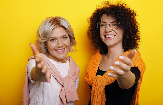 duas mulheres olhando pra frente convidando com as mãos